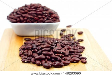 Red bean in white plastic bowl and wooden table. Ingredient bean on white background. Select focus on front stack of bean