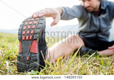 Unrecognizable young runner sitting on grass, stretching his leg. Autumn nature.