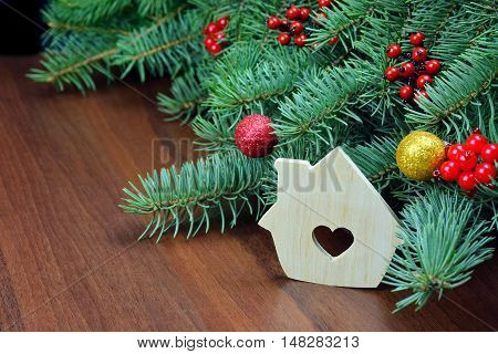 Toy Wooden house handmade near the Christmas tree branches. Christmas Ornaments Made by hand. Festive fantasy. Colorful family holiday. Skill.