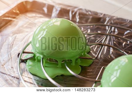Dessert covered in liquid glaze. Green half sphere candy. Preparation of tasty mousse cake. Refreshing taste of mint.