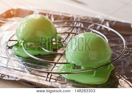 Desserts covered in liquid frosting. Two sweets of green color. Freshly made mint mousse cakes. Mirror glaze recipe.