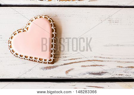 Top view of heart cookie. Biscuit with pink frosting. Taste of true love. Small gift for beloved one.