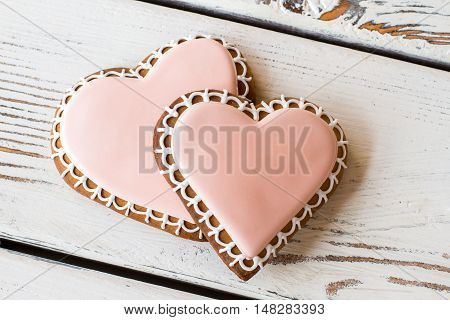 Pair of heart-shaped biscuits. Light pink icing on cookies. Unforgettable taste of love. Small delicious gift.