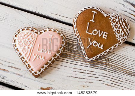 Heart shaped cookies with inscription. Two biscuits on wooden surface. Little symbols of love. How to convey heart warmth.