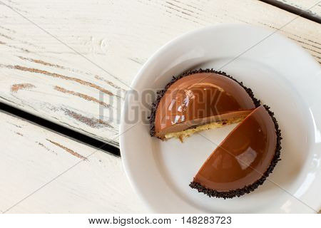 Dessert with mirror icing. White plate with brown cake. Chocolate mousse and soft dough. Freshly made sweet treat.