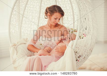 Mother and child on a white chair. Mom and baby boy playing in room. Parent and little kid relaxing at home. Family having fun together.
