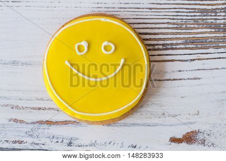 Smiley face cookie. Biscuit with yellow frosting. How to transfer good mood. Dessert that makes you smile.