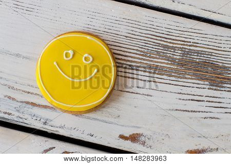 Smiley biscuit on wooden background. Round cookie with glaze. Simplest recipe of great mood. Dessert charges you with energy.