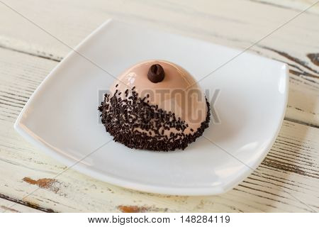 Dome shaped dessert on plate. Dish with mirror icing. Coffee mousse cake with decoration. Plain design and good taste.