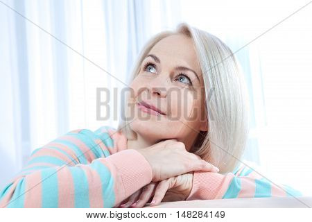 Attractive middle aged woman looking up relaxing at home. Beautiful face close up.