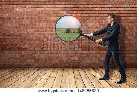 Side view of a businessman looking at red brick wall through a magnifier and seeing nature landscape. Ideas and concepts. Solution and way out. Inspiration.