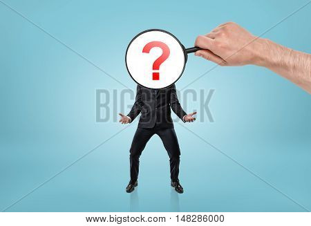 Big man's hand holding magnifying glass in front of question mark-headed businessman. Doubt and uncertainty. Questions and answers. Baffled and puzzled.