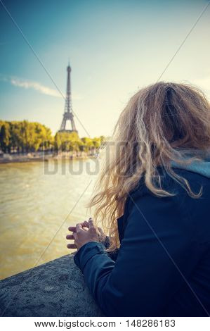 girl standing at the Hay River and looking at the Eiffel Tower. early autumn
