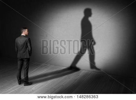 Back view of a businessman looking at his walking shadow on the wall. Moving forward. Ideas and concepts.