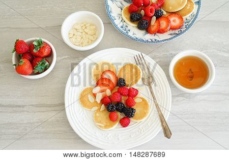 Homemade dutch mini pancakes called poffertjes with strawberries, raspberries and blackberries, sprinkled with blanched sliced almonds and honey. Breakfast scene.