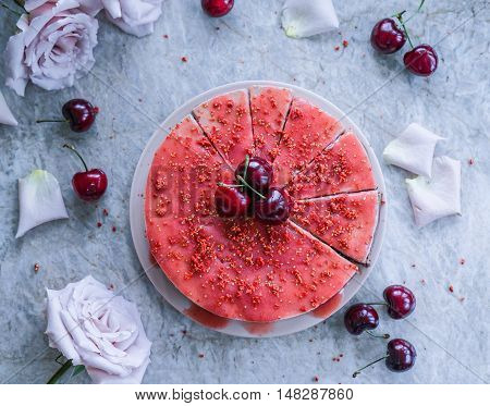 Raw vegan cherry coconut cheesecake gluten-free on a marble background.