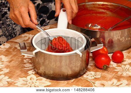 Woman making ketchup, tomatoes boiled to mush pressed through the strainer