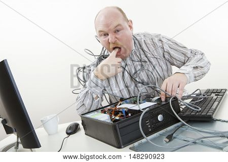 Portrait of irritated businessman licking finger while repairing computer in office