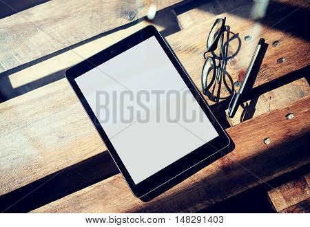 Closeup Modern Tablet White Blank Screen Gadget and Classic Glasses Wood Table Inside Interior Coworking Studio Place.Reflections Natural Background. Blurred