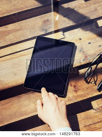 Closeup Mans Hand Touching Home Button Modern Tablet.Black Screen Gadget and Glasses Wood Table Inside Interior Coworking Studio Place.Reflections Natural Background.Vertical