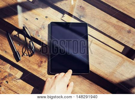 Closeup Mans Hand Touching Home Button Modern Tablet.Black Screen Gadget and Glasses Wood Table Inside Interior Coworking Studio Place.Reflections Natural Background.Horizontal Blurred