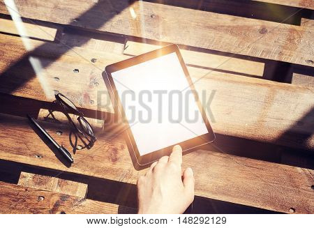 Closeup Mans Hand Touching Home Button Modern Tablet.White Blank Screen Gadget and Glasses Wood Table Inside Interior Coworking Studio Place.Flares Reflections Center. Natural Desk Background