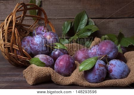 plums in a wicker basket on the sackcloth with blurred background.