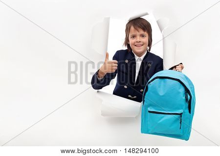 Happy boy showing thumbs up, holding school bag ready to learn new things - copy space