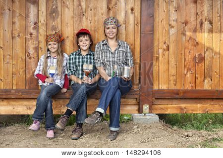 Painting the wood shed - woman and kids ready to do the work, family portrait with copy space