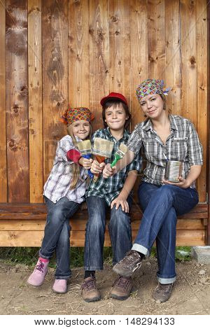 Painting the tool shed - woman and kids ready for the job