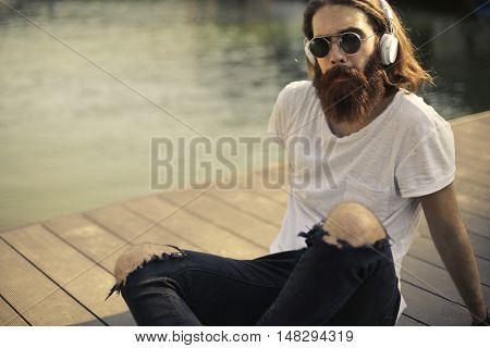 Hipster listening to music through headphones