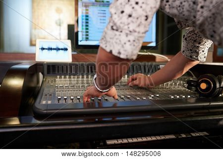 Hands of musician working on music mixer
