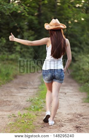 Young girl hitchhiking on the road