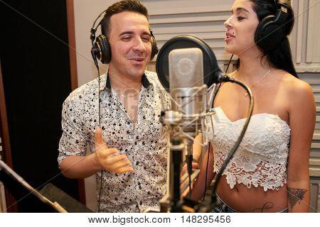 Couple having fun when recording song in studio