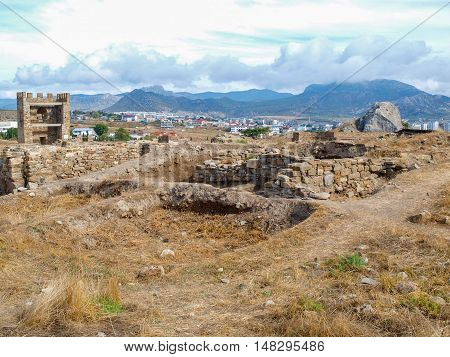 Ancient walls and guard towers on a background of modern buildings in the city of Sudak Crimea