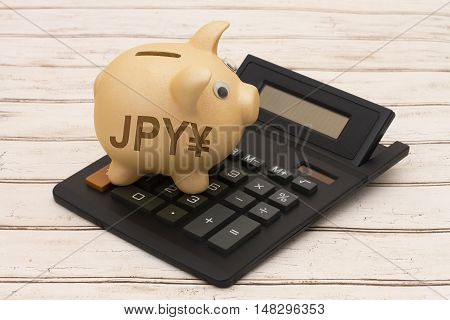 The Japanese Yen currency A golden piggy bank and calculator on a wood background with symbol of yen symbol