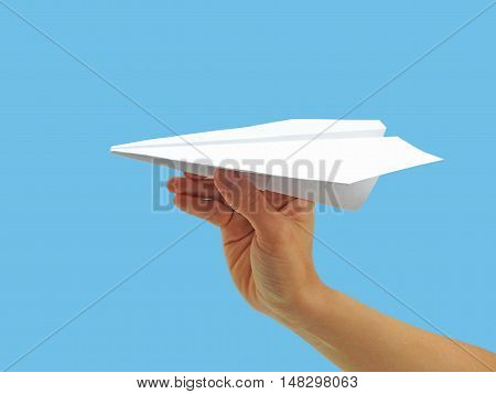 Paper plane in woman hand. Isolated on blue background.