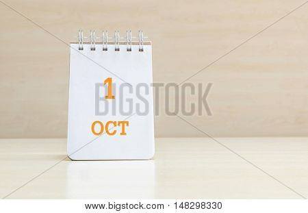 Closeup surface note book with orange 1 oct word in page on blurred brown wood desk and wood wall textured background with copy space under window light
