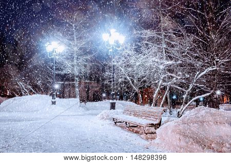 Winter night landscape - snowy bench under frosty winter trees and shining lights. Winter night landscape with winter falling snowflakes. Winter night view with winter snowfall in the winter park.