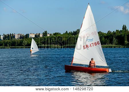 KURCHATOW, RUSSIA - JUNE 23, 2016: Man on sailing boat and windsurfer train on the lake.