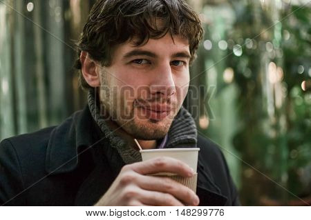 Young handsome man in coat with coffee looking at camera