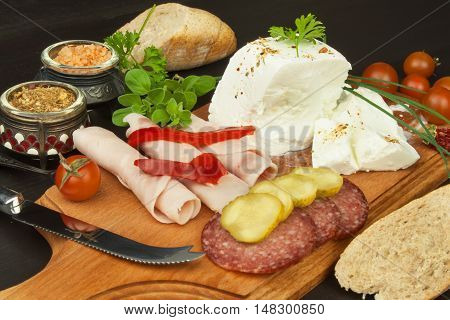 Goat cheese with vegetables and ham. Healthy diet meals for children. Goats cheese on a cutting board.