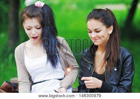 Portrait of two happy young girlfriends with long dark hair. Charming girls having fun in the park lighting candles Bengal