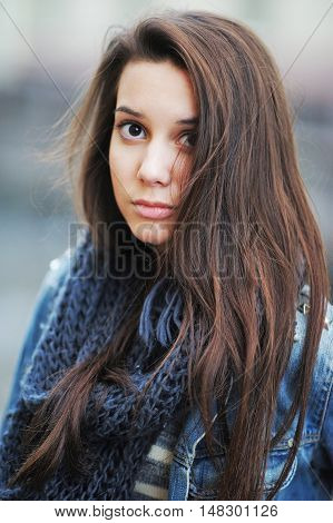 Portrait of a young very cute brown-eyed brunette with long hair in a warm scarf on a cool sunny day close-up