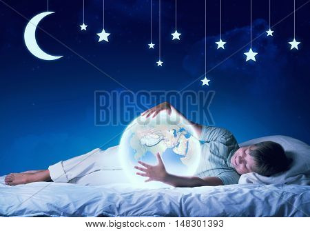Cute boy in bed looking at glowing Earth planet. Elements of this image are furnished by NASA