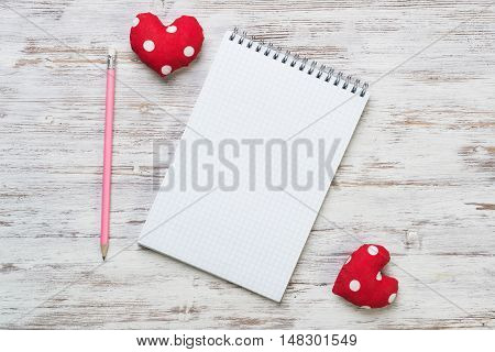 Hearts and blank notepad with pencil on wooden table