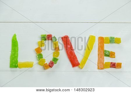 Love word with candied fruits on wooden white background
