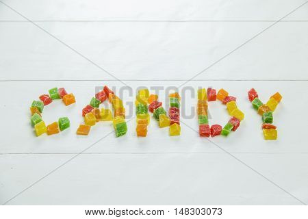 Word candy written with dried pineapples on white background