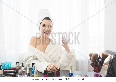 Young beatiful woman doing manicure, sitting at dressing table at home.