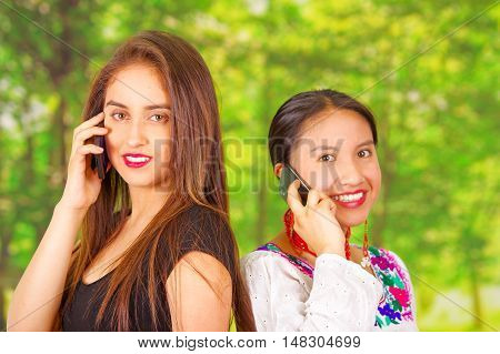 Two beautiful young women posing for camera, one wearing traditional andean clothing, the other in casual clothes, rubbing backs and both talking on mobile phones, park background.